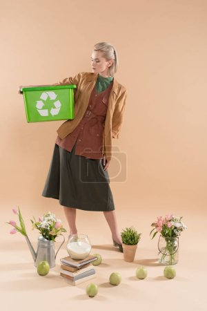 Photo for Blonde woman holding recycling box near plants and flowers on beige background, environmental saving concept - Royalty Free Image