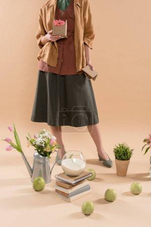 Photo pour Vue recadrée de femme tenant maison en carton avec fleur près de plantes et de fleurs sur fond beige, environnement économie concept - image libre de droit