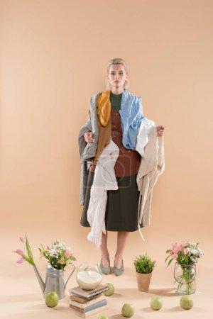 Photo pour Blonde femme tenant eco vêtements près de plantes et de fleurs sur fond beige, environnement économie concept - image libre de droit