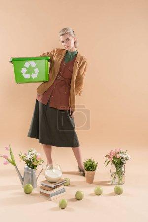 Foto de Mujer hermosa caja reciclaje cerca de plantas y flores sobre fondo beige, ambiental ahorro concepto - Imagen libre de derechos
