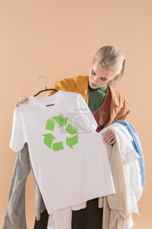 Photo for Young woman looking at eco clothing with recycling sign on hanger isolated on beige, environmental saving concept - Royalty Free Image