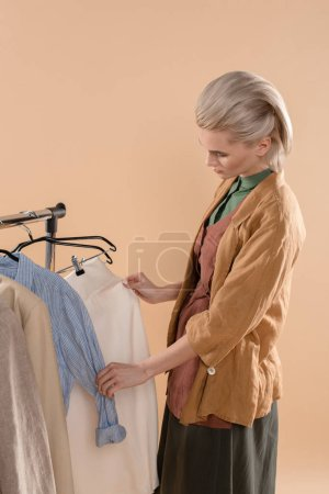 Photo for Blonde woman choosing eco clothing isolated on beige - Royalty Free Image