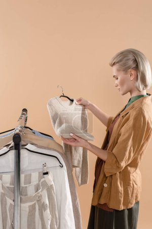 Photo for Blonde woman holding eco clothing isolated on beige - Royalty Free Image