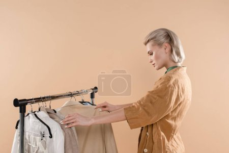 Photo for Blonde woman looking at eco clothing isolated on beige - Royalty Free Image