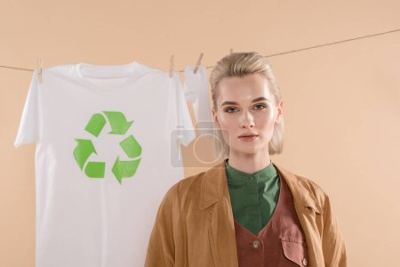 Foto de Enfoque selectivo de mujer rubia de pie cerca de calcetines y una camiseta con reciclaje signo en tendedero aislado en beige, ambiental ahorro concepto - Imagen libre de derechos
