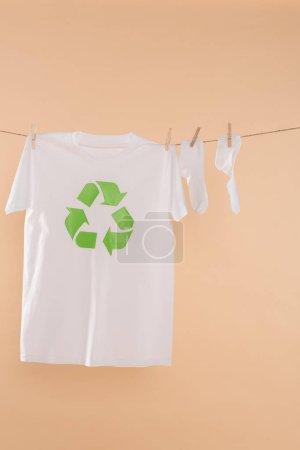 Photo pour Chaussettes blanches près de t-shirt avec recyclage signe sur corde à linge isolé sur beige, concept d'épargne écologique - image libre de droit
