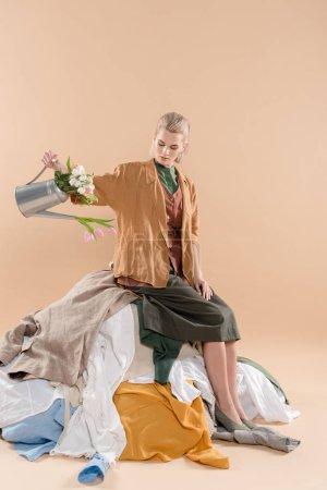 Photo pour Blonde femme assise sur une pile de vêtements et d'exploitation arrosoir avec fleurs sur fond beige, environnement économie concept - image libre de droit