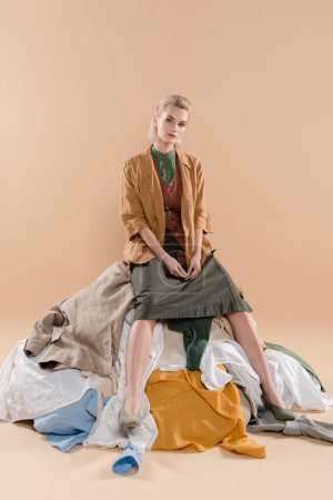 Photo for Blonde woman sitting on pile of clothing on beige background, environmental saving concept - Royalty Free Image