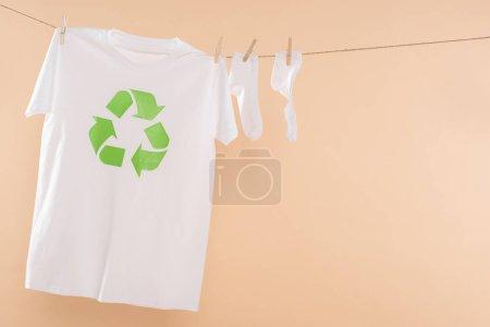 Foto de Camiseta con reciclaje signo en tendedero cerca de calcetines blancos aislados en concepto de ahorro amarillento, medio ambiente - Imagen libre de derechos