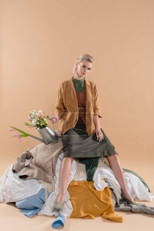 Photo pour Blonde fille assise sur une pile de vêtements et d'exploitation arrosoir avec fleurs sur fond beige, environnement économie concept - image libre de droit