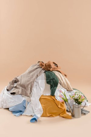 Photo for Stack of clothing near watering can with flowers on beige background, environmental saving concept - Royalty Free Image