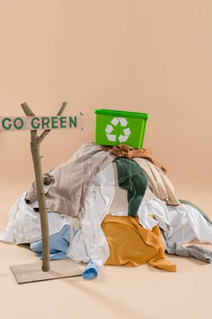 wooden sign with go green lettering near recycling box on pile of clothing on beige background, environmental saving concept