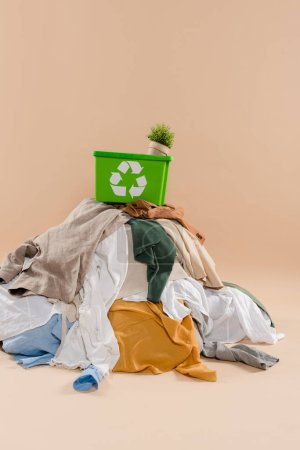 green recycling box with plant in pot on stack of clothing on beige background, environmental saving concept