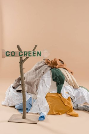 Photo for Wooden sign with go green lettering near pile of clothing on beige background, environmental saving concept - Royalty Free Image