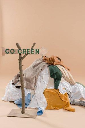 Foto de Cartel de madera con ir verde Letras junto a la pila de ropa sobre fondo beige, concepto ahorro ambiental - Imagen libre de derechos