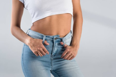 Photo for Partial view of slim young woman in jeans and crop top on grey background - Royalty Free Image