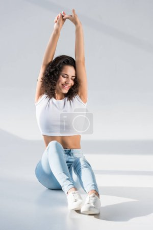 Photo for Laughing woman in jeans stretching with closed eyes on grey background - Royalty Free Image
