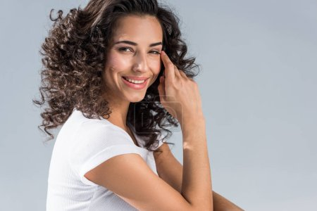 Photo for Happy curly girl looking at camera isolated on grey - Royalty Free Image