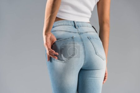 Photo for Cropped view of shapely girl in blue jeans isolated on grey - Royalty Free Image