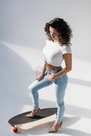 Photo pour Curly femme en jeans et récolte supérieure se tenant sur longboard sur fond gris - image libre de droit