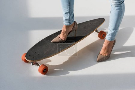 Photo for Cropped view of woman in high-heeled shoes standing on longboard - Royalty Free Image