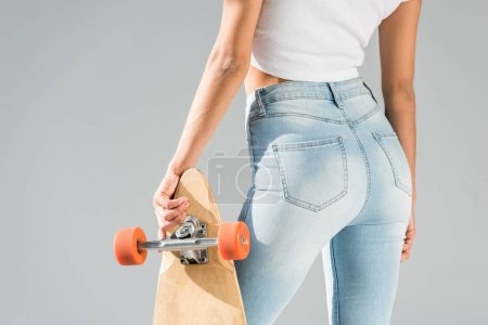 Photo for Cropped view of sexy girl in jeans with longboard isolated on grey - Royalty Free Image