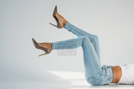 Photo for Partial view of young woman in jeans and high-heeled shoes on grey background - Royalty Free Image