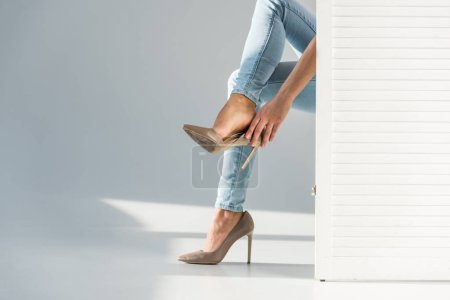 Photo for Partial view of woman putting on high-heeled shoes behind room divider on grey background - Royalty Free Image