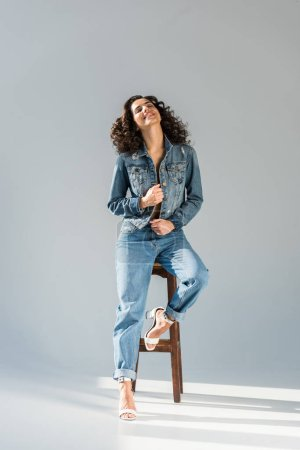 Photo for Blissful young woman in jeans and jacket sitting on wooden chair on grey background - Royalty Free Image