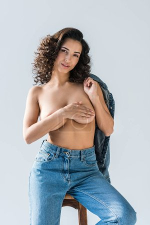 Sensual sexy girl in jeans sitting on chair and covering breasts with hand on grey background