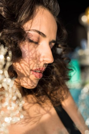Photo for Curly relaxed woman with closed eyes on blur background - Royalty Free Image