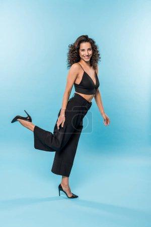 Photo pour Gracieuse jeune femme en vêtements noirs, debout sur une jambe sur backgorund bleu - image libre de droit