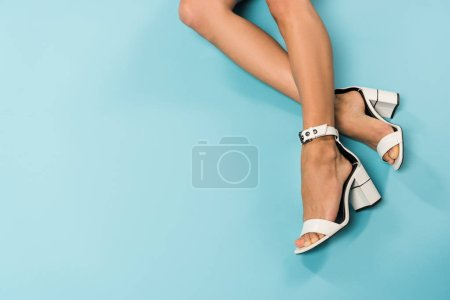 Photo for Partial view of woman in white sandals on blue background - Royalty Free Image