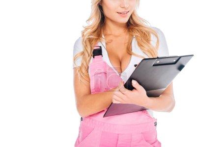 Photo pour Vue recadrée de l'architecte femme en uniforme rose avec presse-papiers isolé sur blanc - image libre de droit