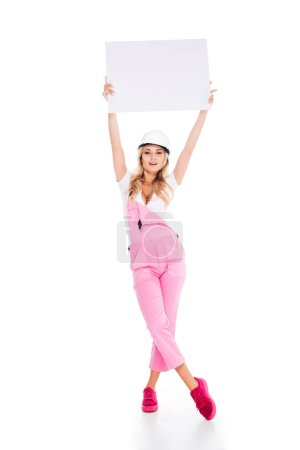Photo for Attractive handy woman in pink overalls, hardhat holding over head placard on white background - Royalty Free Image