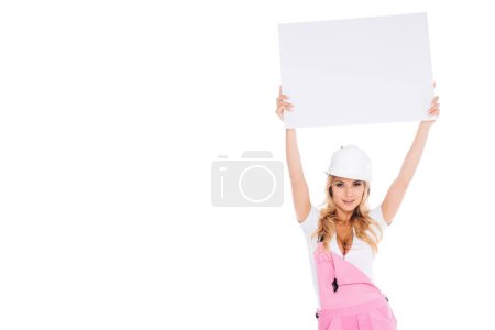 Photo for Handy woman in pink uniform, hardhat holding over head empty placard  isolated on white - Royalty Free Image