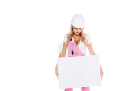 Photo for Blonde handy woman in pink uniform, hardhat holding placard isolated on white - Royalty Free Image