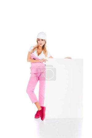 Photo for Attractive woman in pink uniform, hardhat holding placard on white background - Royalty Free Image