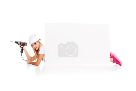 Photo for Blonde handy woman in pink uniform and hardhat with screwdriver lying behind placard on white background - Royalty Free Image