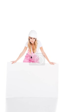 Photo for Blonde handy woman in pink uniform standing behind placard on white background - Royalty Free Image