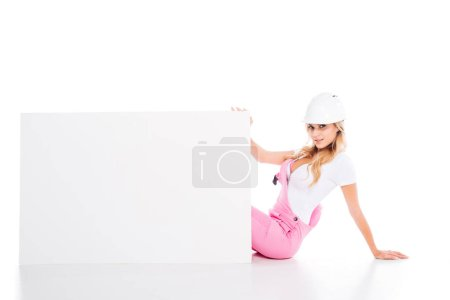 Photo pour Femme pratique en uniforme rose assis derrière une pancarte sur fond blanc - image libre de droit