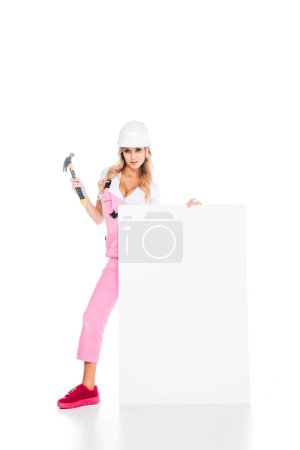 Photo for Blonde handy woman in pink overalls standing behind placard with hammer on white background - Royalty Free Image