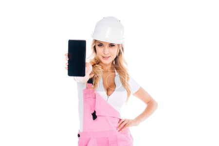 Photo for Blonde handy woman in pink overalls, hardhat standing and holding smartphone with blank screen isolated on white - Royalty Free Image