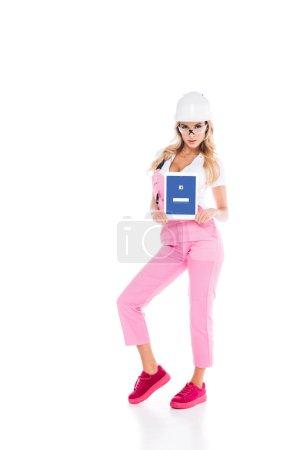 Photo pour Attrayant pratique femme en uniforme rose tenant tablette numérique avec application facebook à l'écran sur fond blanc - image libre de droit