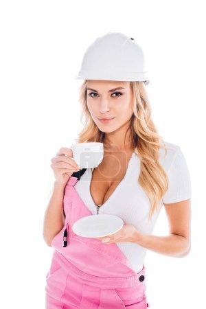Photo pour Jolie femme très pratique en rose uniforme et hardhat boire de tasse isolé sur blanc - image libre de droit