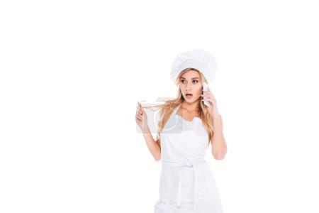 Photo pour Femme séduisante blonde cook en uniforme debout ang parler sur smartphone isolé sur blanc - image libre de droit