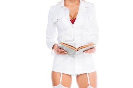 Photo pour Vue recadrée de l'infirmière en manteau court, bas et sous-vêtements rouge tenant livre isolé sur blanc - image libre de droit
