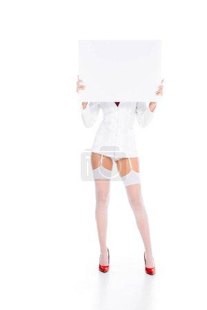 Photo pour Infirmière en bref manteau, bas et rouge chaussures tenant vide affiche blanc sur fond blanc - image libre de droit