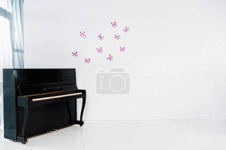Foto de Piano negro sobre fondo blanco con mariposas color púrpura y el espacio de copia - Imagen libre de derechos