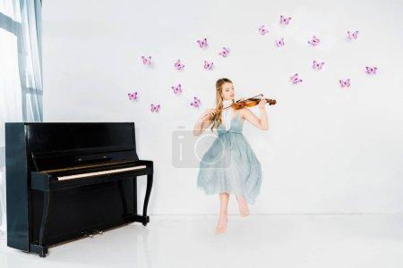 Foto de Chica flotante en vestido azul tocando violín en fondo blanco con mariposas color púrpura - Imagen libre de derechos